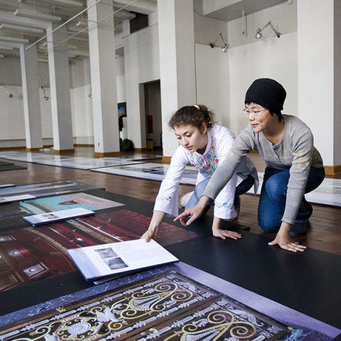 Young female student laying out photos of cultural artifacts with older woman in a gallery setting