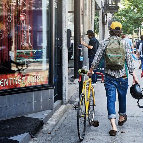 Photo of student wearing cap walking with yellow bike on city sidewalk