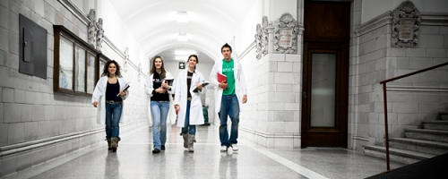 Four students in lab coats walk down the hall of the Strathcona Anatomy and Dentistry Building