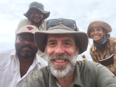 Anthropology professor in field with 3 individuals in the background