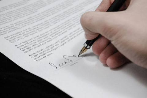 Someone signing a document