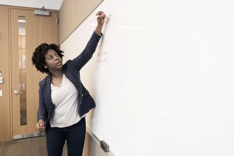 Professor writing on a white board