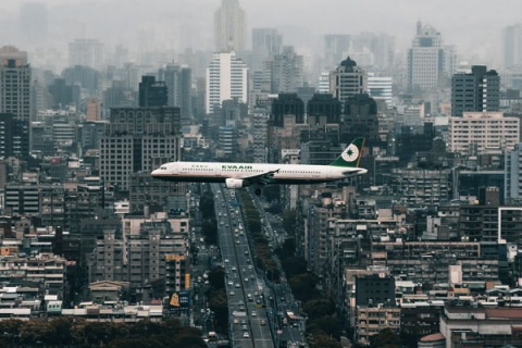Photo of an airplane over a city