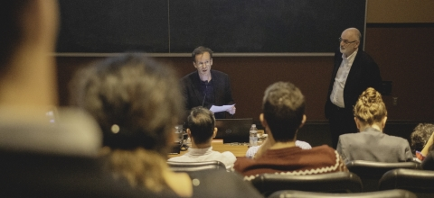 Two professors lecturing a classroom of students.
