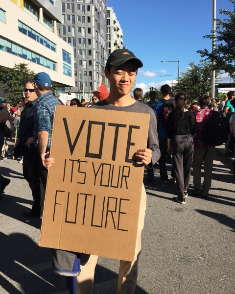 """Student holding up a sign written """"Vote it's your future"""" in a crowd of people."""