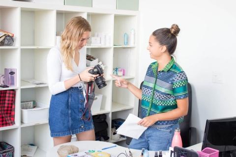 Photo of two interns working in an office, one of them holding a camera