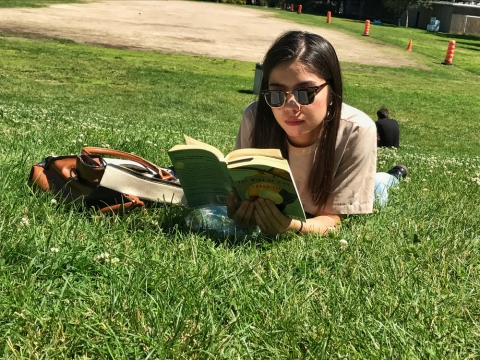 Arts student reading a novel on the green grass of the main field