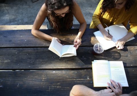 Students reading at a picnic table