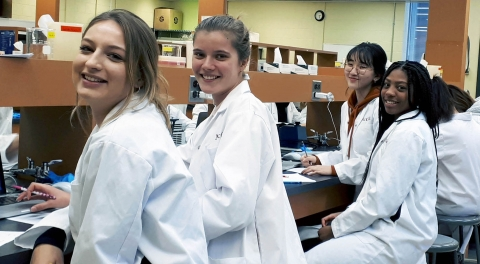 students sitting at a lab bench in lab coats