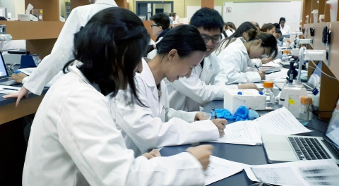 students in lab coats sitting at a bench