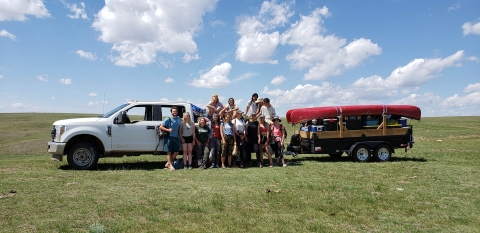 students standing in front of truck in a field