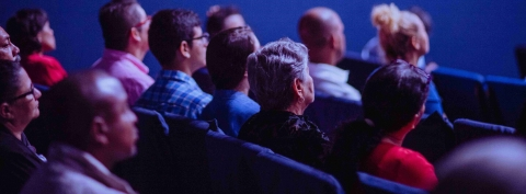 People sitting in the audience looking ahead