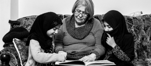 A woman teaching 2 children how to read.