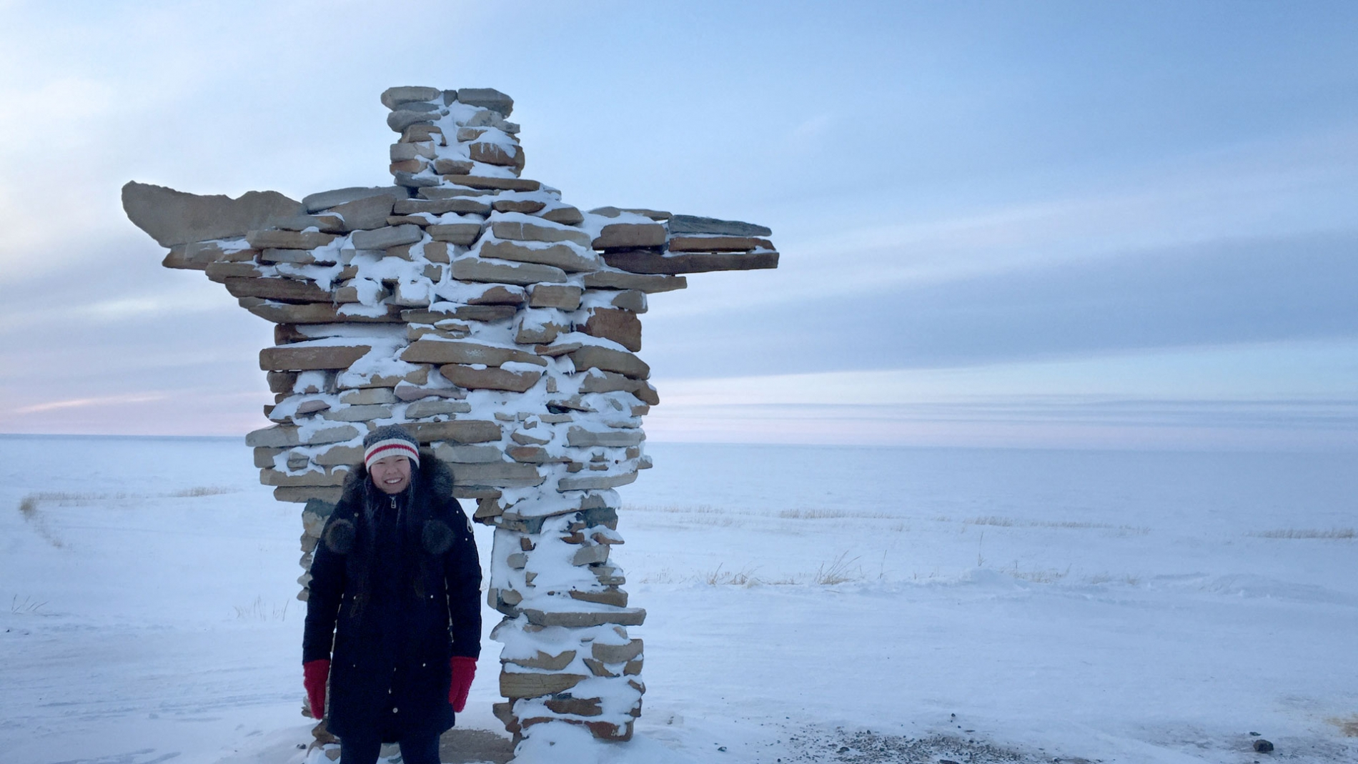 Christine Ha in front of an inuksuk