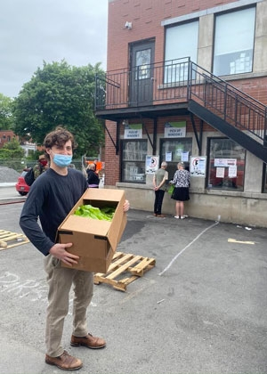 Photo of Tristan, with mask, delivering a box to Meet the Need Montreal