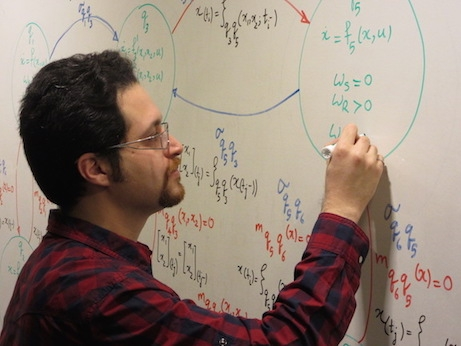 man writing equations on whiteboard
