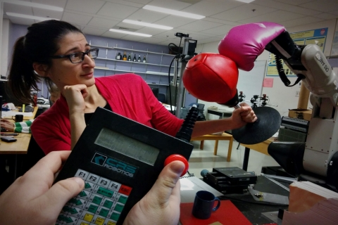 woman interacting with a robotic boxing glove with it's controls held in the foreground