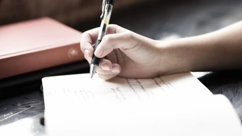 Photo of someone writing on paper