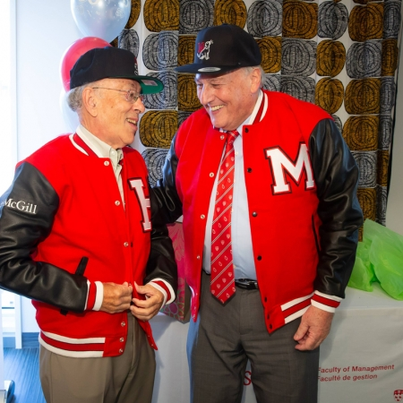 Henry Mintzberg and Morty Yalovsky try on their gifted caps and varsity jackets.