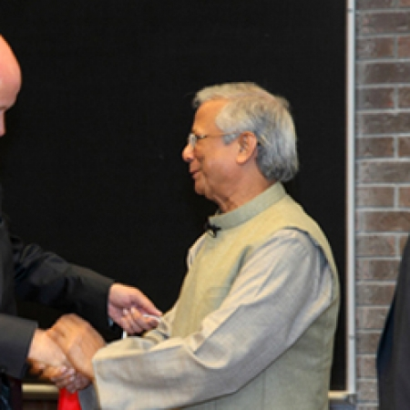 Prof. Moore presents Dr. Yunus with a gift from the Desautels Faculty of Managem