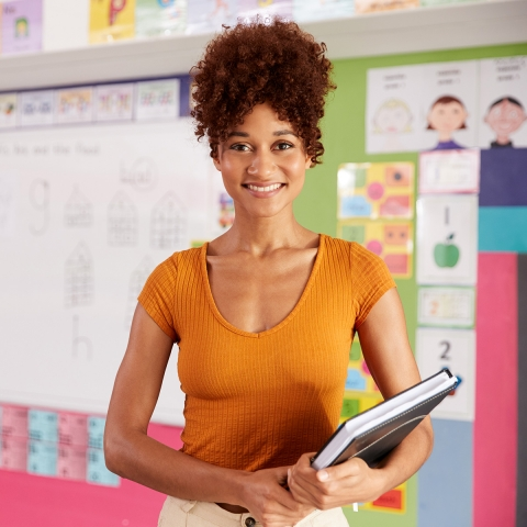 Black female teacher holds a book in a brightly coloured classrooms