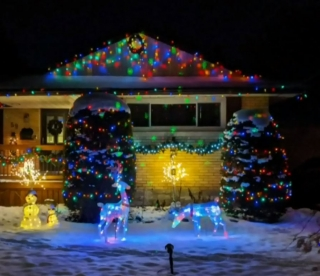 Suburban home with Christmas lights and lighted reindeer and snowmen on the lawn