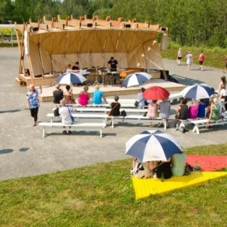 Sustainable wood stage with an audience sitting on benches and coloured triangle wood structures