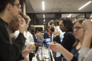 Photo of students presenting their projects during an event and speaking with attendees.