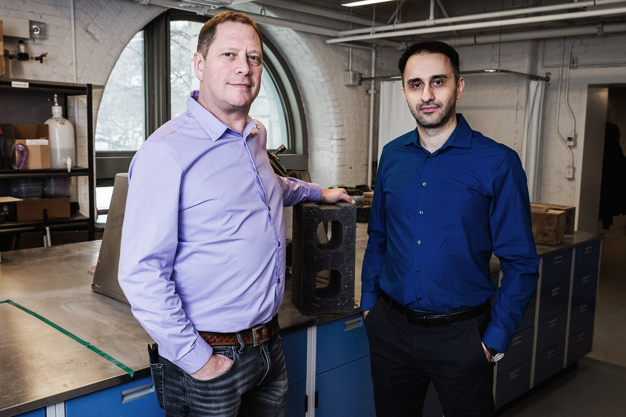 Mehrdad Mahoutian and Chris Stern of Carbicrete posing for a photo in a workshop with a carbon-negative block on table