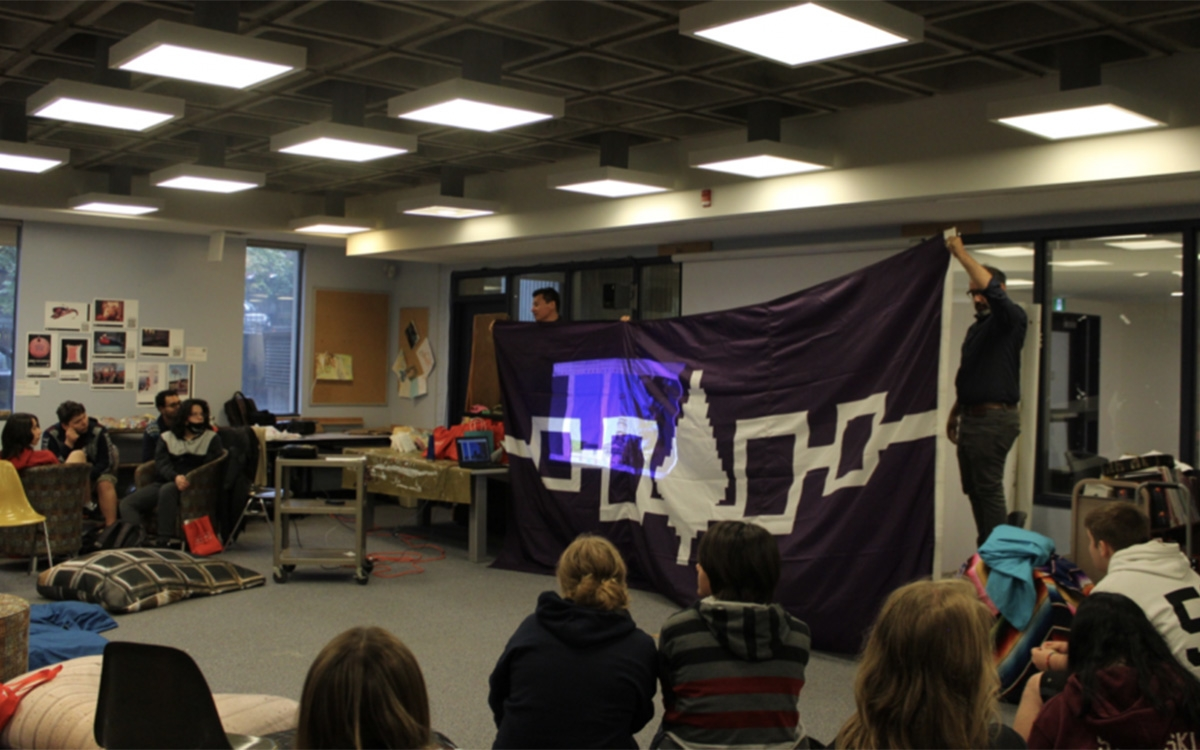 2 students holding the Hiawatha Wampum Belt Flag in front of a group of students