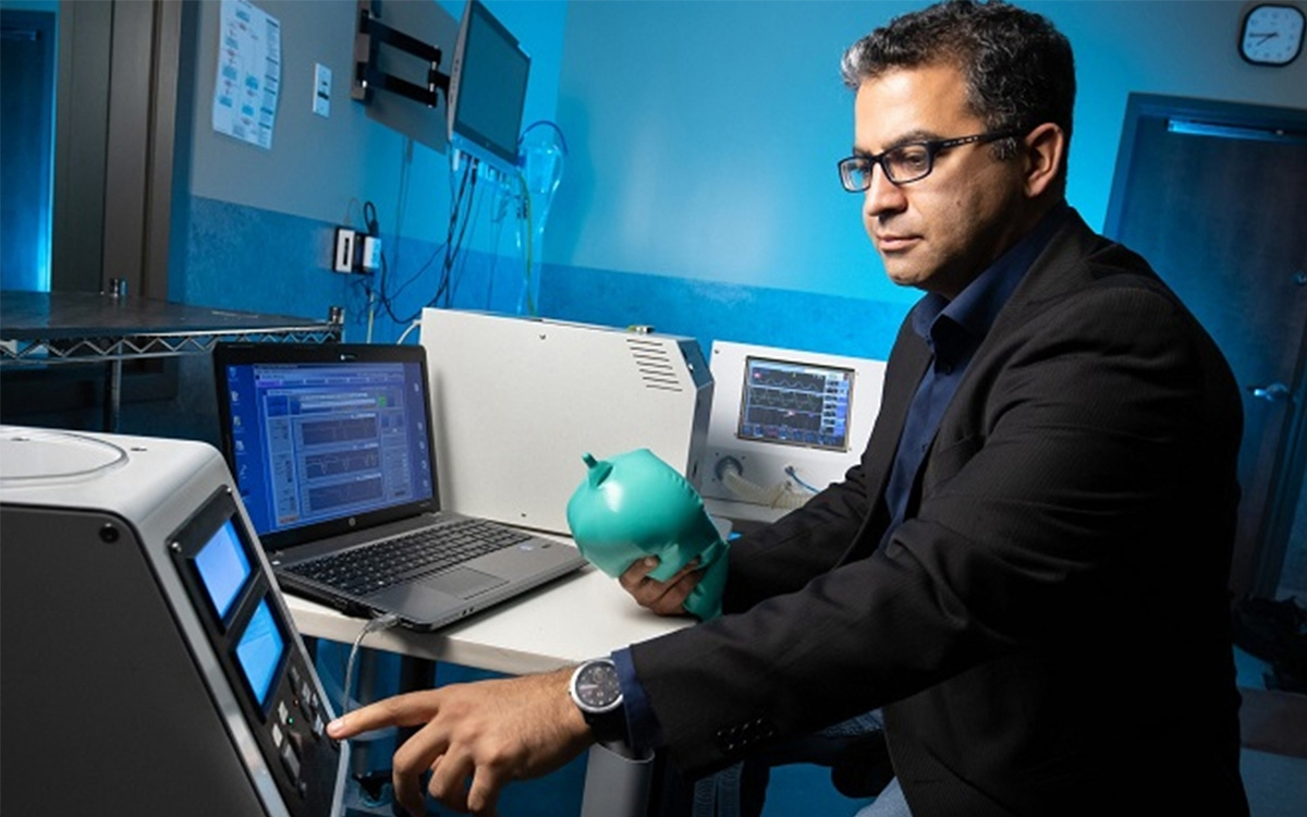 Dr. Reza Farivar holds a ventilator prototype while touching a computer screen