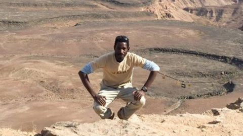 Graduate student Moses crouches at edge of rock canyon