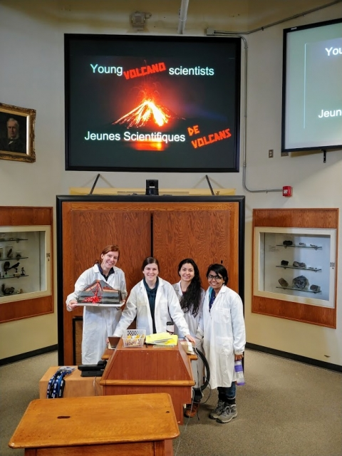 "Four graduate students in lab coats holding volcano props in front of a screen with the words ""Young Volcano Investigators"""