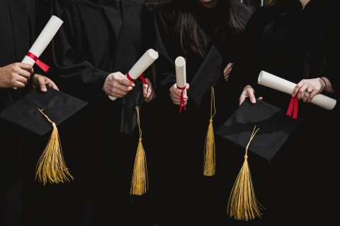 Students with graduation caps and diplomas