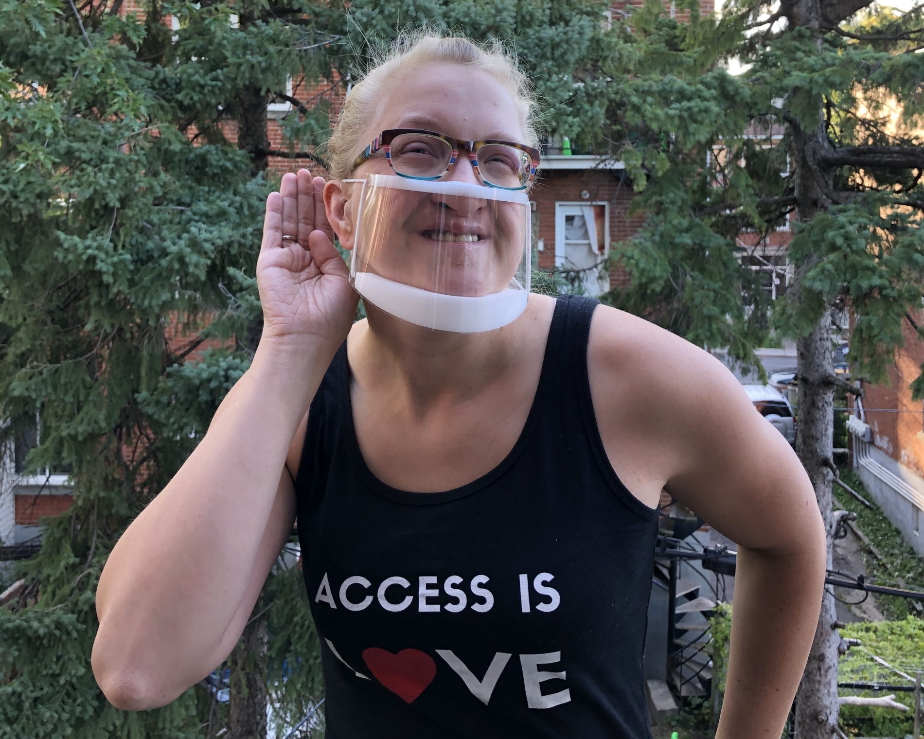 """Woman wearing clear mask, with hand cupped behind her ear, wearing a t-shirt that says """"Access is Love"""""""