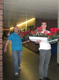 Adrian Spuehler and Daniel Sutherland holding poinsettias