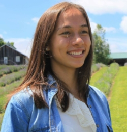 Allyson Kis - young woman with shoulder length brown hair wearing a denim jacket and standing in a field