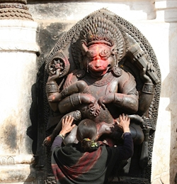 woman kneeling in front of a statue of a deity
