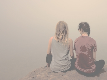 Two students sitting on a mountain top
