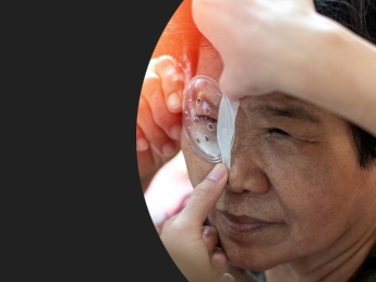 Elderly Asian woman getting a clear eyepatched installed on the right hand side of a black box