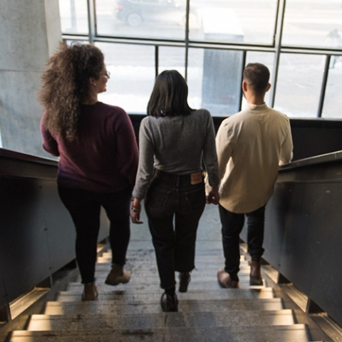 Three grad students walk down stairs at McGill's Music building