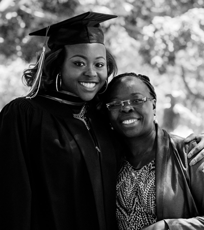 female graduate and relative hugging (in black-and-white)