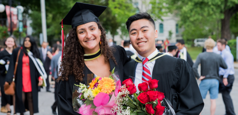 male and female graduates holding flowers
