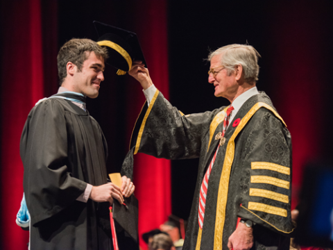 graduate being tapped on the head by chancellor