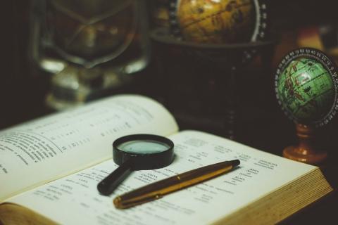 Book, magnifying glass, pen, globe, lamp