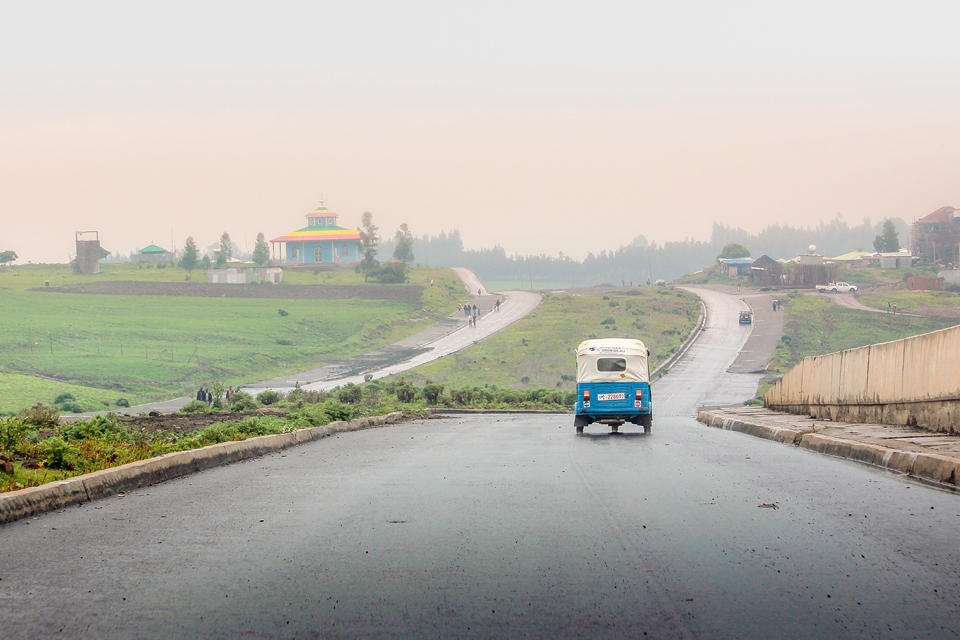 Ethiopian landscape: a tricycle transport driving on a wet road on a misty day, with an Orthodox church in the distance. Photo by Solen Feyissa.