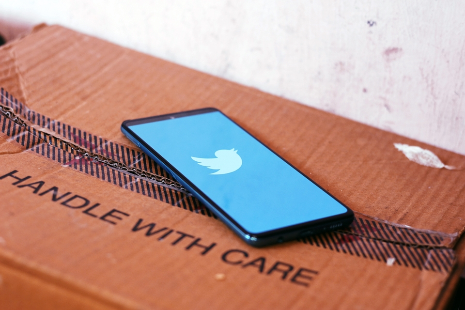 Black tablet showing the blue and white Twitter logo on top of a cardboard box with 'handle with care' stamped on a lid flap. By Ravi Sharma, via Unsplash.