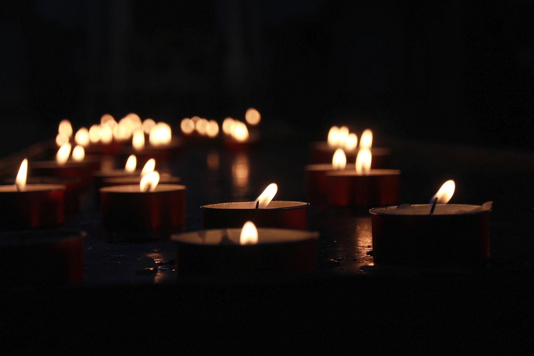 Votive candles illuminate the darkness