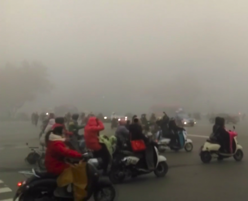 crowded Beijing street full of motorbikes and vehicles in the smog
