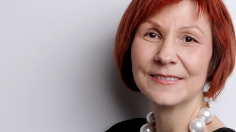 A photo of Professor Blackstock, a woman with short red hair and a pearl necklace, against a white background